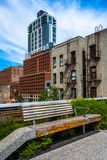 Bänk och gamla byggnader som ses från den höga linjen, Manhattan som är ny Royaltyfri Foto