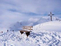 Bänk och kors överst av berget i fjällängar royaltyfri fotografi