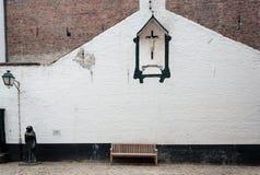 Bänk och kors i Beguinagen Belgien Arkivbilder