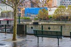 Bänk på flodbanken på regnig dag Royaltyfria Foton