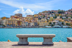 Bänk på sjösida i Porto Santo Stefano, Argentario, Tuscany, I Arkivbilder