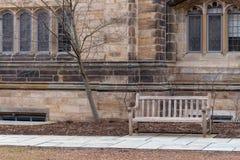 Bänk på stengångbanan mot gammal dekorativ byggnad arkivfoto