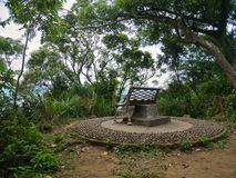 Bänk på stenplattformen som omges av träd royaltyfri bild