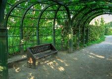 Bänk som förläggas under bågen av träd i parkera Royaltyfri Bild