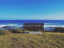 Bänk som ut ser över havet Arkivfoto