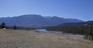 Bänk vid en flod och berg Royaltyfria Foton