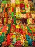 Bänkar av godisar av former och olika färger i en marknad av Barcelona i Spanien Arkivfoton