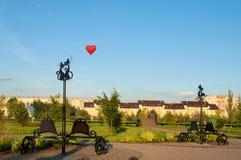 Bänkar med skulpturer av förälskade katter i parkera av den 45th årsdagen av Akron i Veliky Novgorod, Ryssland Arkivbilder