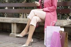 bänkcelltelefon som sitter genom att använda kvinnan Arkivbilder