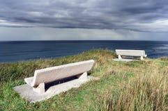 Bänke auf Klippe nahe dem Meer mit stürmischen Wolken Lizenzfreie Stockfotos