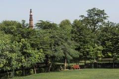 Bänken i arkeologiska Mehrauli parkerar och Qutub Minar som ses i bakgrund Arkivbild