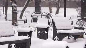 Bänken i en snöfallstad parkerar stock video
