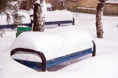 Bänken i gården täckas med snö under ett tungt snöfall i staden royaltyfri foto