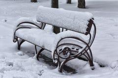 Bänken i parkera täckas i snö Royaltyfri Bild
