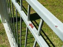 Bänken i parkerar, rost på det vita staketet, det rostiga staketet i parkerar, utanför trädgårds- gräs bakom royaltyfri foto