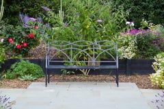 Bänkplats på trädgårds- uteplats med blommor Arkivbilder