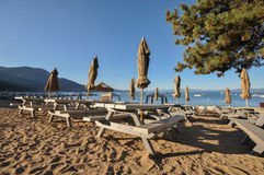 Bänktabeller med paraplyer vid laken på sanden Royaltyfri Bild