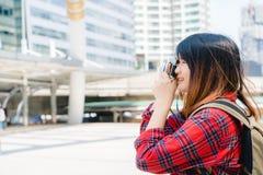 Bär den asiatiska kvinnan för den lyckliga härliga handelsresanden ryggsäcken Unga glade asiatiska kvinnor som använder kameran t Arkivfoto