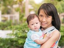 Bär den asiatiska modern för skönhet gulligt behandla som ett barn i trädgårds- utomhus- Arkivbilder