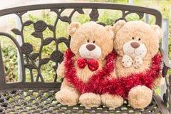 Bär des Weihnachtsgeschenks zwei mit Feier auf Bank Stockfotografie