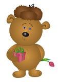 Bär in einer Schutzkappe gibt eine Blume Lizenzfreie Stockfotografie