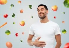 Bär frukt den rörande magen för den lyckliga fulla mannen över att falla Arkivbilder