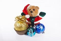 Bär gekleidet als Santa Claus mit Geschenk und Weihnachtsdekorationen Lizenzfreie Stockbilder