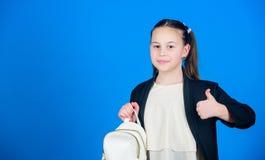 Bär liten trendig cutie för flickan ryggsäcken Begrepp för ungemodetrend Formell stilkläder för skolflicka med litet arkivbild