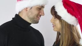 Bär lyckliga par för julferie det röda för den santa för det nya året locket hatten, mannen och kvinnaförälskelseleendet som ser