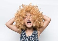 Bära en blond peruk och en rolig ansiktsuttryckasiatflicka royaltyfri foto