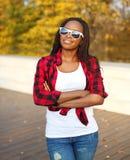 Bära för kvinna för stående härligt le afrikanskt solglasögon, röd rutig skjorta i solig höst arkivbild