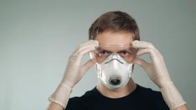 Bära för man en maskering bär skyddande exponeringsglas skydd av andningsorgan och ögon från förorening arkivfilmer