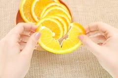 Bära frukt i en träbunke i hans sönderrivna apelsin för handen som är klar för consum Royaltyfria Bilder