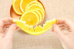 Bära frukt i en träbunke i hans sönderrivna apelsin för handen som är klar för consum Arkivfoton