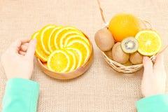 Bära frukt i en träbunke och korg, skyttlar för handinnehav på Arkivfoto