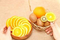 Bära frukt i en träbunke och korg som rymmer händer på skyttlar Arkivfoto