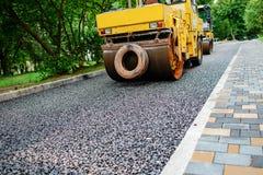 Bära ut reparationsarbeten: asfaltera rullen som staplar, och trängande varma lägger av asfalt Maskin som reparerar vägen Royaltyfri Bild