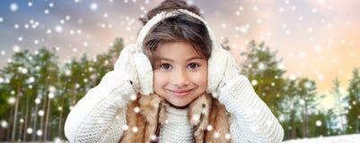 Bärande öronskydd för liten flicka över vinterskog arkivbilder