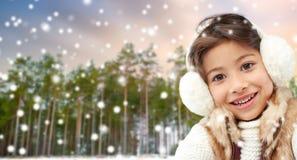 Bärande öronskydd för liten flicka över vinterskog royaltyfri foto