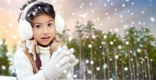 Bärande öronskydd för liten flicka över vinterskog arkivfoto