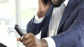 Bärande affärsdräkt för svart man som övar på den stationära cykeln som talar på telefonen stock video
