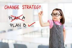 Bärande affärsklänning för gullig liten flicka och dra att ändra för strategi för affärsplan Kontorsbakgrund Arkivbild