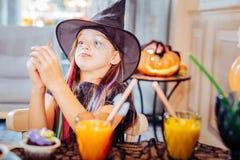 Bärande allhelgonaaftondräkt för härlig flicka som spelar trick, medan äta klibbiga sötsaker royaltyfria bilder