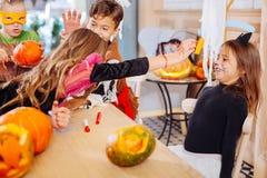 bärande allhelgonaaftonklänning för Mörker-haired flicka som spelar trick med hennes mer unga syster royaltyfri foto
