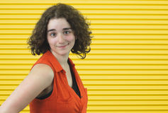 Bärande apelsin för ny ung flickabrunett på gul bandbakgrund fotografering för bildbyråer
