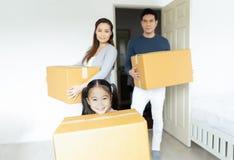 Bärande askar för lycklig familj in i nytt hem på rörande dag på på suddig bakgrund flytta sig för begrepp royaltyfri bild