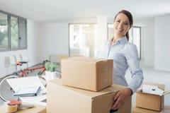 Bärande askar för lycklig kvinna in i hennes nya kontor Royaltyfri Foto