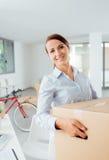 Bärande askar för lycklig kvinna in i hennes nya kontor Royaltyfria Foton
