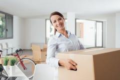 Bärande askar för lycklig kvinna in i hennes nya kontor Royaltyfria Bilder