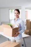Bärande askar för lycklig kvinna in i hennes nya kontor Royaltyfri Bild